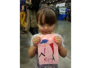 A young Fairegoer with her light-up card.