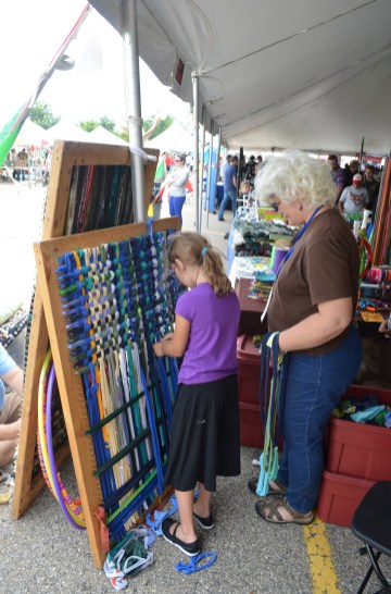 A member of the White family teaches a young maker the craft of weaving. The Whites had three booths at the Faire featuring weaving, marshmallow guns, and jewelry.