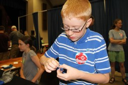 William Wakely, one of the youngest makers at our Faire, assembles one of his scale maille flowers.