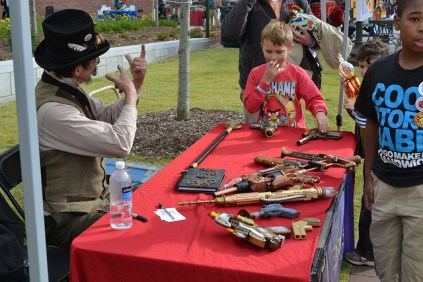 A young maker stares at the steampunk-era guns with envy.