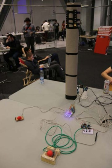 This 2 player speed-testing game had the crowd cheering during the demo, earning the team third place in the hackathon. Players watched the changing LED cube, and when it started to flash, the first player to hit their red button would be awarded a point. The first to light all their tower lights won the game. The tower was constructed with discarded drink cans!
