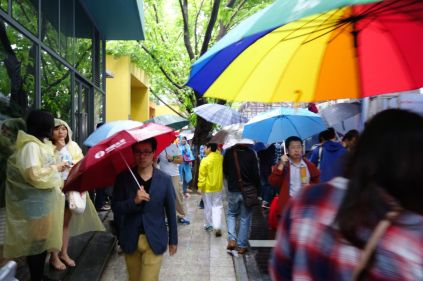 Umbrellas were out on a rainy first day.