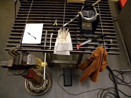 The welding setup: clamps, vise, file, wire brush, wire cutters, 5356 weld rod, leather gloves, auto-darkening hood, and jacket. I was spoiled with a Miller Synchrowave 350LX.