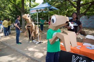 Cole Hartnett, 11, releases his inner dinosaur with KitRex; this model is a 15-foot-long velociraptor costume made of cardboard.