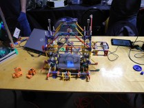 A K'Nex built printer with a couple of its prints.