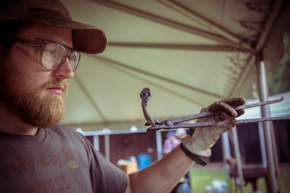 A blacksmith shows off the nail he intends to place in the Nail Tree.