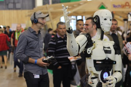 An open-source 3D printed life-sized robot called InMoov waves to the crowd.