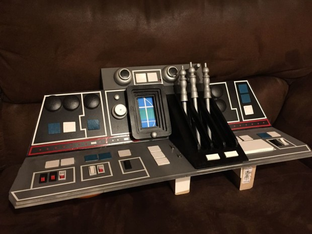 The dashboard of this Millennium Falcon cockpit is outfitted with an eclectic mix of switches, wheels, and dowels.