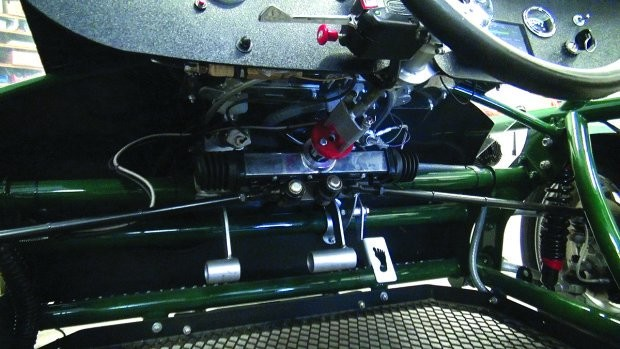Under the dash: dual brake pedals, steering linkages, and accelerator — step on it, but don't call it a gas pedal. Photo by Sam Euston.