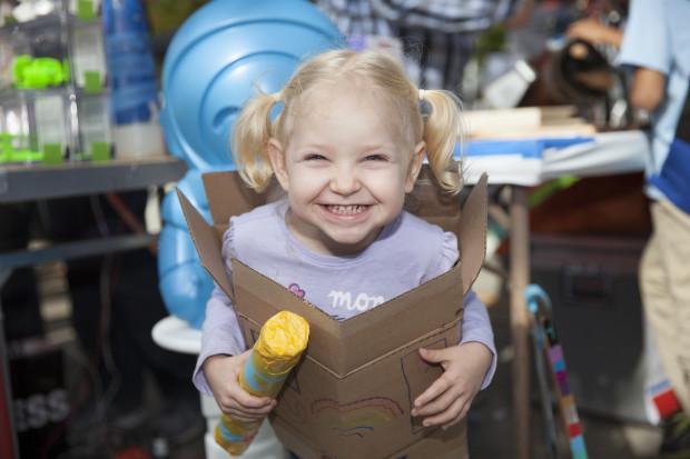Young girl inside cardboard box