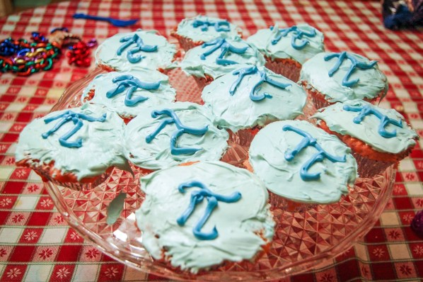 A plate of light blue cupcakes with the mathematical symbol for pi frosted onto them.