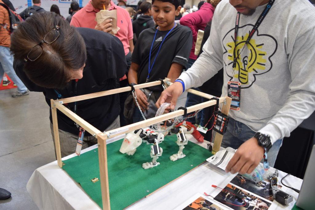 Moore explaining one of his robots. Photo courtesy of Jeffrey Moore