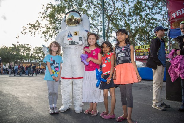 Four small children stand around a suited up astronaut.