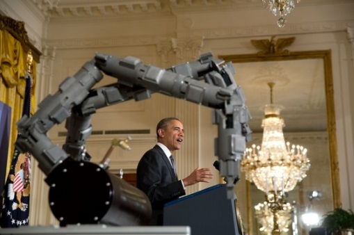President Obama announces a new advanced manufacturing initiative while a 3D printed robotic arm fabricated at Oak Ridge National Laboratory poses in the foreground. Official White House Photo by Lawrence Jackson