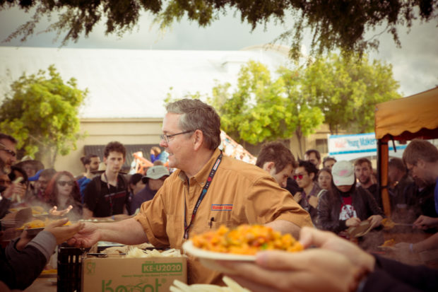 Dale Dougherty hands a plate of paella to a waiting patron while in the foreground another person holds a plate.