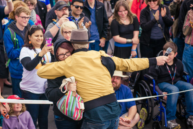 Adam Savage hugs a young fan in the crowd.