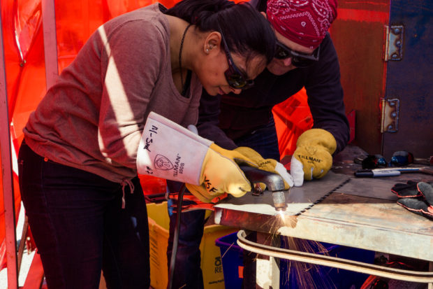 A young woman cuts a piece of sheet steel with a plasma torch while the instructor looks on.