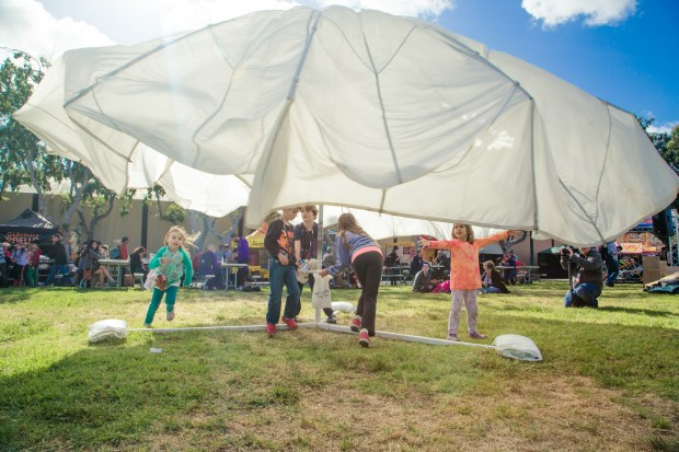 Young children running underneath a spinning parachute held aloft by a frame.