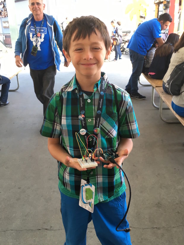 A proud young Maker, showing off his creation.