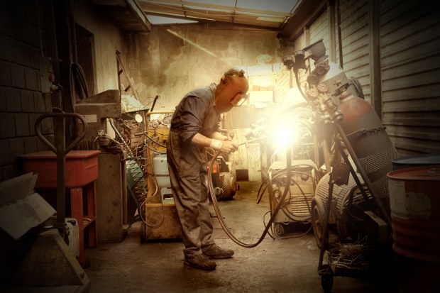 A man welding in a small crowded workshop
