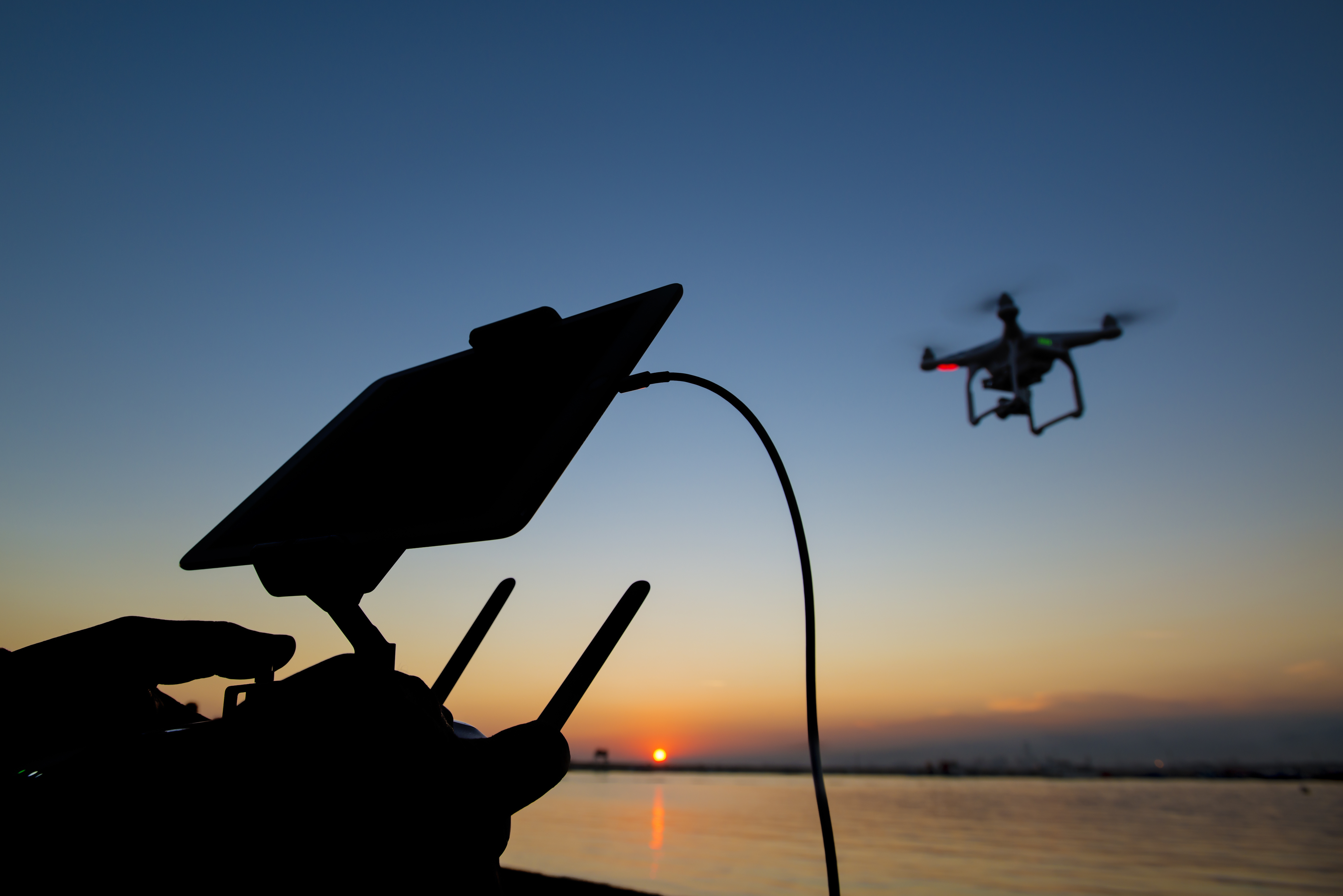 silhouette of airborne drone and pilot's controller against setting sun over ocean.