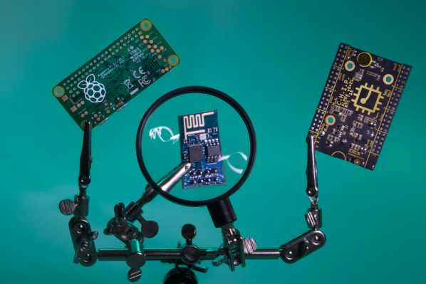 A helping hands holding a Raspberry Pi, a CHIP, and a magnifier on an ESP8266