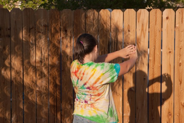 A young girl facing a fence looks at her shadow and the shadow of a tree where all the light holes are eclipse shaped.
