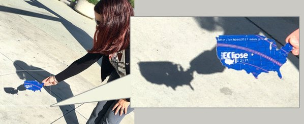 A young girl holds out a 3D printed pinhole viewer in the shape of the USA, and her shadow shows the eclipse.