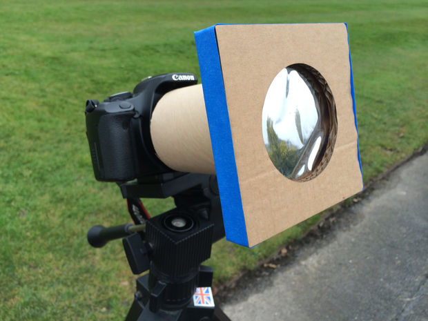 A telephoto lens on a camera in a grassy field has a cardboard and solar film filter constructed on top of it.