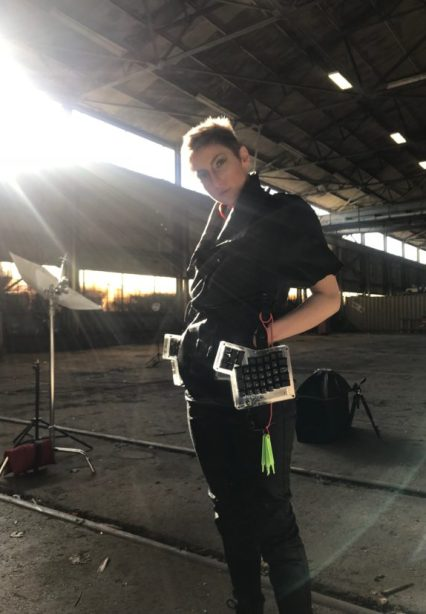 A woman in a black jumpsuit stands with the sun behind her wearing a split computer keyboard in a harness.