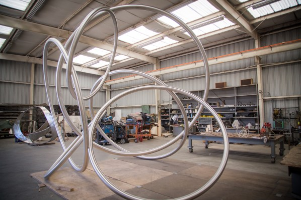 A large abstract sculpture of intersecting metal rings stands in a roomy warehouse.