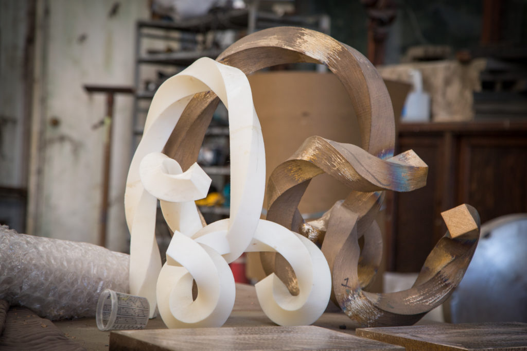 Two matching sculptures rest on a table, one white 3D printed, and one cast bronze.