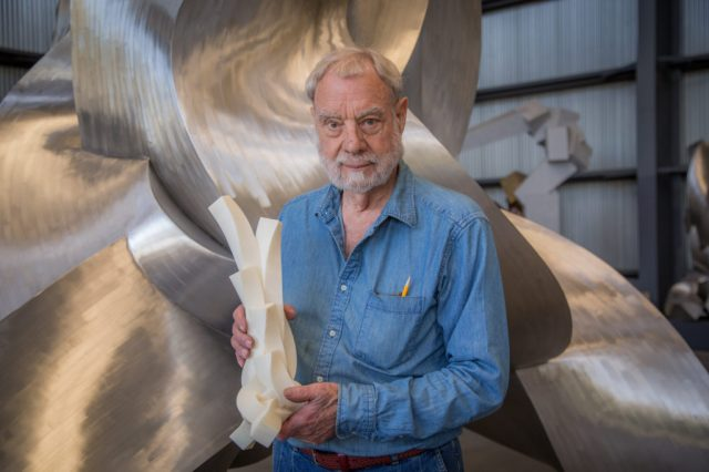 Bruce Beasley stands holding a 3D printed version of the giant abstract twisted metal sculpture behind him.