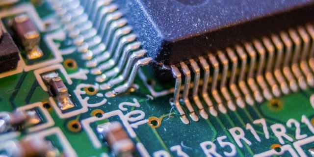 An upclose macro photograph of a chip SMD soldered to a circuit board