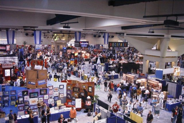 people fill a convention hall of booths