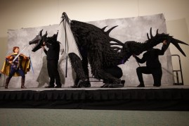 A young knight fights a black dragon