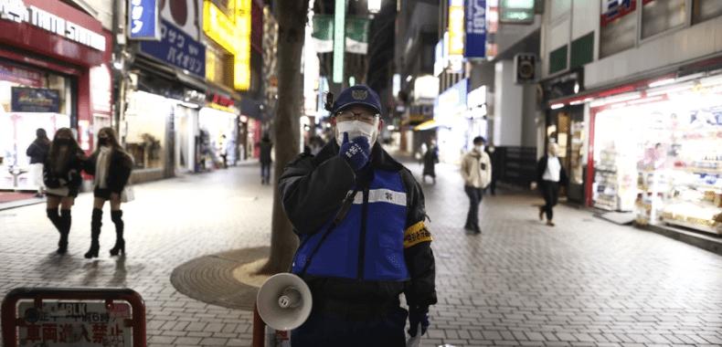 警察官が新宿でステイホームを呼び掛けている写真