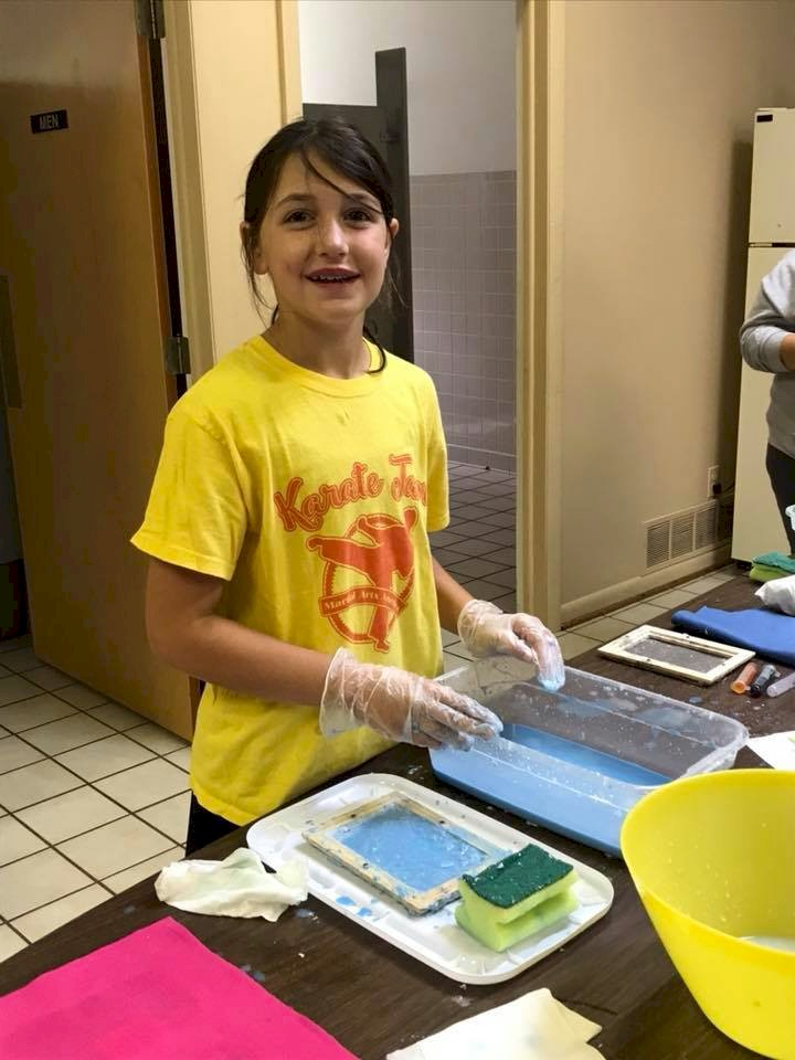 Cadette Girl Scout making paper.
