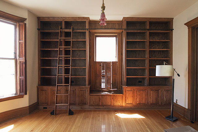 the built in bookshelves and rolling ladder in the library making it lovely