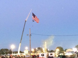 the Stars and Stripes fly over the tractor pull