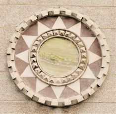 Portland Stone framed roundel with central disc of Connemara Marble and radiating triangular segments of Cork Red Marble and white Donegal Marble