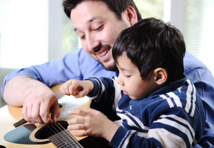 Father and son playing guitar at home