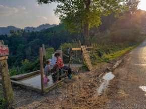 峠道の路傍の集落の水道で洗濯する子供