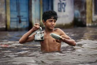 Steve McCurry,INDIA. Porbandar. 1983. Tea Vendor carries tea kettle in waist deep monsoon water.