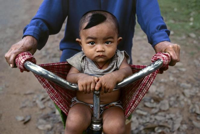 Steve McCurry,CAMBODIA. Angkor. 2000. Baby in a bicycle sling at Banteay Srei.