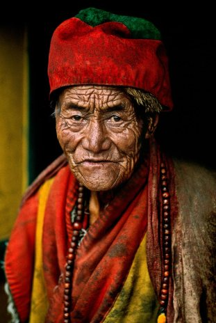"Steve McCurry,TIBET, Monk at Jokhang temple, Lhasa, Tibet, 2000'There was something about his face,' McCurry has said of this monk at the Jokhang temple in Lhasa, Tibet. There was some 'ancient feeling, some kind of ancient truth there. I have never seen a face quite like his.' He looks with intensity into McCurry's camera, deeply aware of the transience of the moment.""The lines of time trace a deep personal history across this old monk's face. It seems as though his has been a life of enquiry, a quest for a truth, on a higher level. He looks into the lens of the camera with a searching gaze. That is what attracted McCurry, as he visited the Jokhang Temple on his photographic pilgrimage through Tibet, sketching with his camera the various pathways to the Buddha. - Phaidon 55Magnum Photos, NYC31836, MCS2000009 K001Phaidon, 55, Looking East, The Path to Buddha, Iconic Images, final print_milan, final book_iconic"