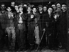 Emaciated male prisoners, victims of Nazi genocide, staring through barbed wire fence at their liberators after American forces overran the Buchenwald concentration camp.