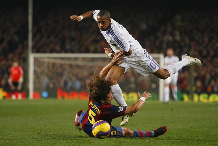 Real Madrid's Robinho is challenged by FC Barcelona's Carles Puyol during the Spanish League soccer match, FC Barcelona vs Real Madrid at the Camp Nou Stadium in Barcelona, Spain.
