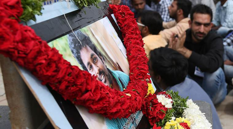 Students listen to a speaker as they protest the death of an Indian student, portrait in front, who, along with 4 others, was barred from using some facilities at the Hyderabad university in Hyderabad, India, Wednesday, Jan 20, 2016.The protesters accused Hyderabad University's vice chancellor along with a federal minister of unfairly demanding punishment for the five lower-caste students after they clashed last year with a group of students supporting the governing Hindu nationalist party. (AP Photo /Mahesh Kumar A.)