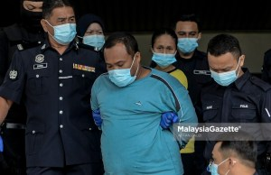 The two suspects, Mohd. Fadzli Abdull Razak (stepfather) and Zuraida Atan (mother) are escorted by the police from the Melaka Criminal Investigation Department (CID) to the Ayer Keroh Courts Complex to face charges for murdering and abusing Zubaidi Amir Qusyairi Abd. Malek. PIX: AFFAN FAUZI / MalaysiaGazette / 10 FEBRUARY 2021